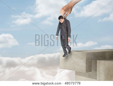 Giant hand dropping off a businessman over the clouds on a structure