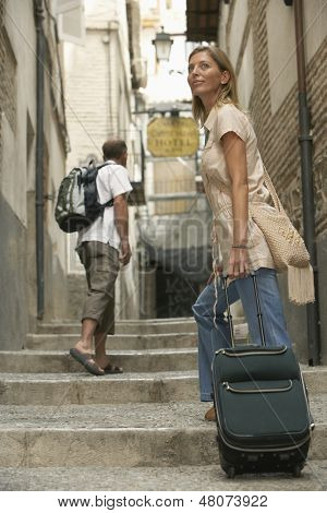 Happy middle aged woman with luggage moving upstairs in alley with man in background
