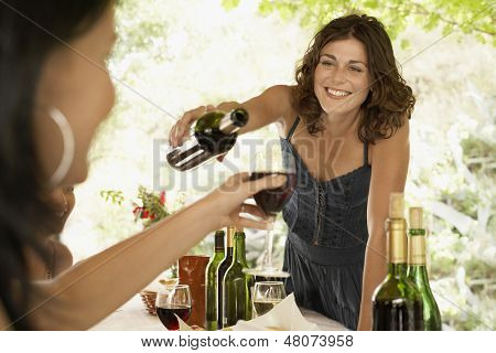 Beautiful young woman serving red wine to female friend in party