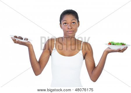 Conflicted woman deciding to eat healthily or not on white background