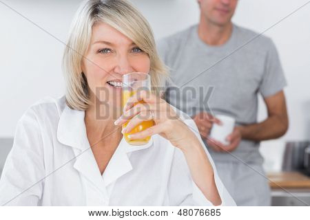 Blonde drinking orange juice in kitchen with partner standing behind