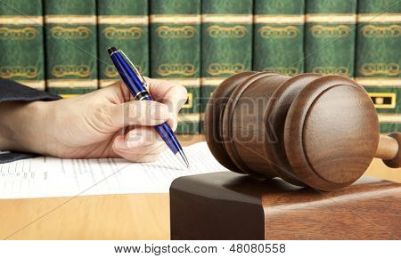 Female hand writes the document in court