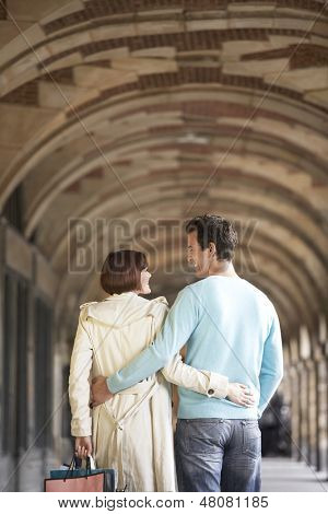 Rear view of a couple with arms round each other walking through archway