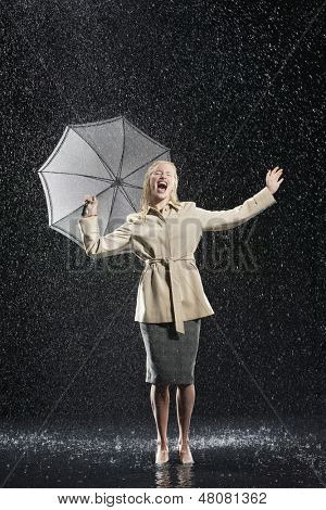 Full length of a young businesswoman in overcoat with umbrella singing in the rain