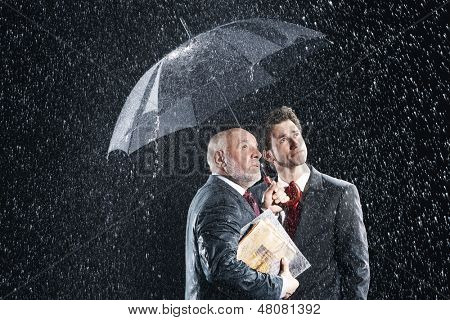 Young and middle aged businessmen watching rain from under umbrella