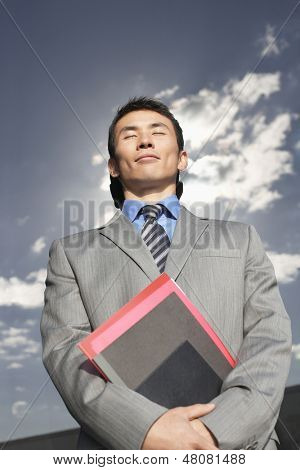 Low angle view of a smiling businessman against reflective wall with folders and eyes closed
