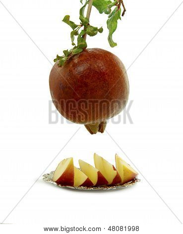 Pomegranate and slides of apple on white