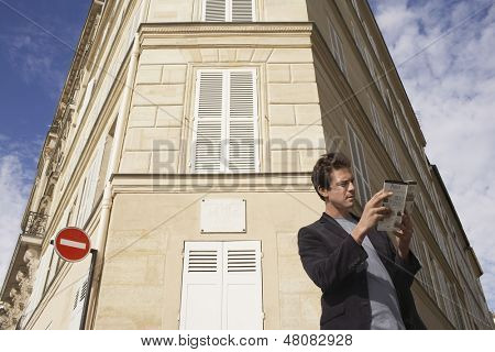 Low angle view of a man reading guidebook in front of apartment