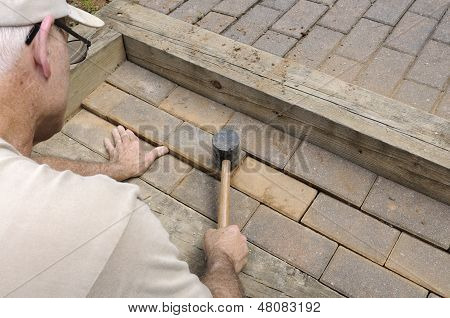 Worker Using Mallet to Install Brick Walkway