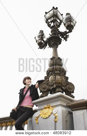 Low angle view of a young woman leaning on ornate streetlight against the sky