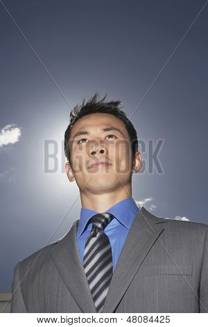 Low angle view of a smiling young businessman against sky