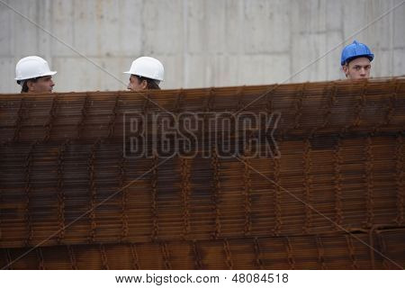 Three construction workers behind a stack of rebar