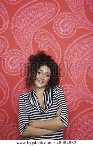Portrait of a teenage girl in striped top standing against colorful wallpaper