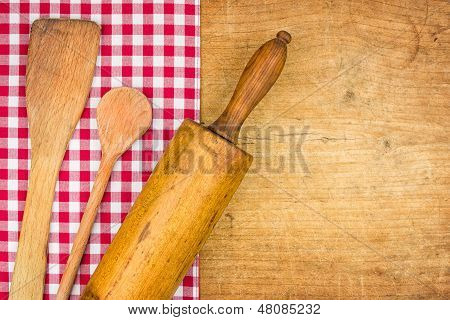 Rolling pin with wooden spoon on a wooden board with a checkered tablecloth