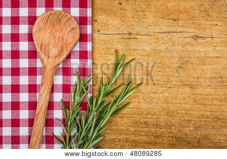 Fondo de madera rústica con mantel a cuadros y cuchara de madera