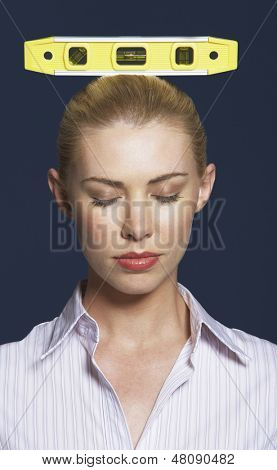 Closeup of a businesswoman balancing spirit level on head against blue background
