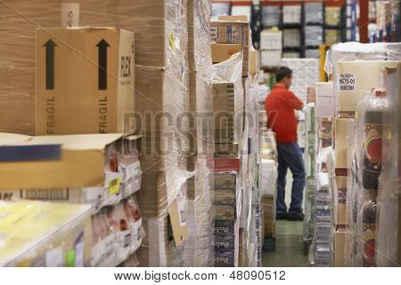 Warehouse full of cellophane wrapped goods with man in the background