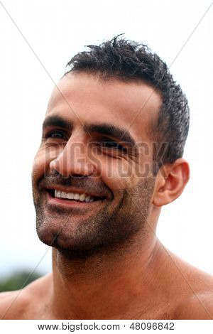 A close up portrait of a shirtless handsome man with a beard who is smiling and looking away