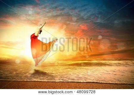 Image of female ballet dancer against sunset background soaring above water waves