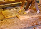 stock photo of overalls  - Construction worker thermally insulating house attic with glass wool - JPG