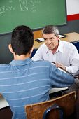 Mature professor looking at male high school student at desk in classroom