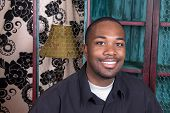 image of male face  - An African American smiling while resting in his living room - JPG