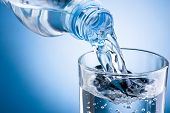 picture of bottles  - Pouring water from bottle into glass on blue background - JPG