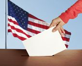 Female hand with ballot and box on Flag of USA