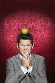 Young man cringing with apple on his head against red velvet background