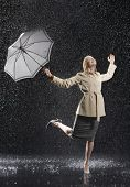 stock photo of dancing rain  - Full length of a young businesswoman in overcoat with umbrella enjoying the rain - JPG