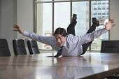 image of mischief  - Young businessman sliding on stomach on conference table - JPG