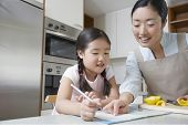 Mother assisting girl with her homework in the kitchen
