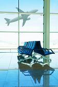 stock photo of terminator  - Seats in airport terminal with airplane behind the window - JPG