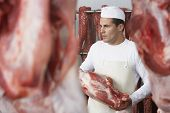Butcher holding slab of meat in the meat locker