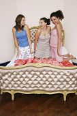 picture of slumber party  - Teenage girls at slumber party kneeling on funky bed - JPG