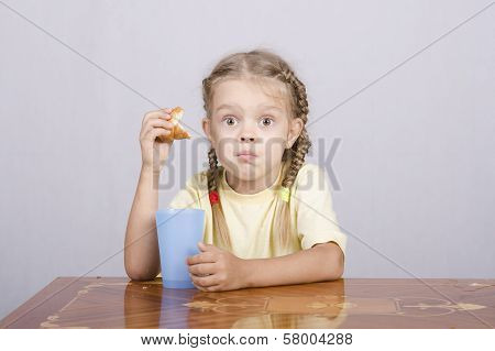 Girl Eating A Muffin With Juice At The Table