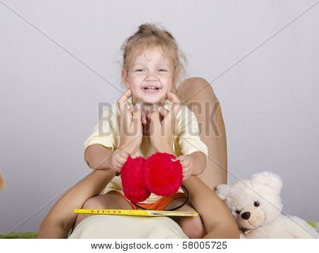 Little Girl Sitting On Mom And Laughs