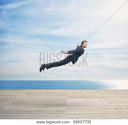 Man in suit flying over boardwalk