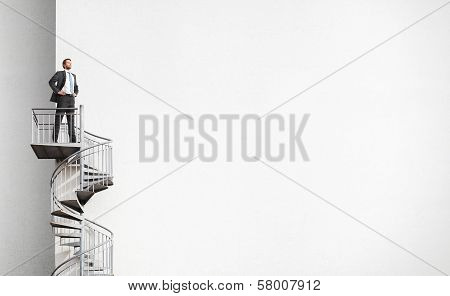 Businessman standing on spiral staircase