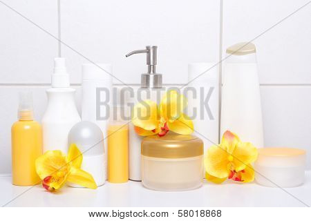 Set Of White Cosmetic Bottles And Hygiene Supplies With Orange Flowers Over Tiled Wall