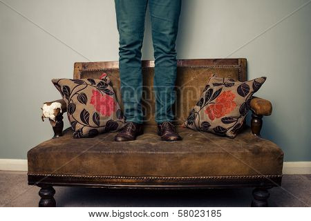 Man Standing On Sofa And Wearing His Shoes