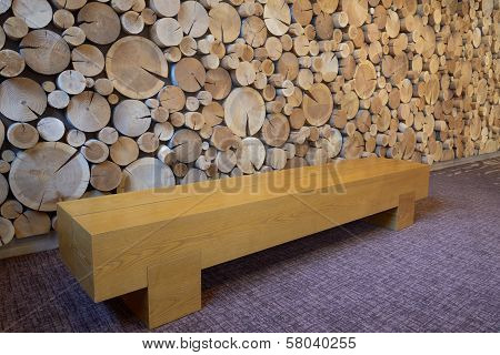 Wooden bench with logs background