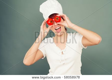 Female Cook Holding Tomatoes On Her Eyes