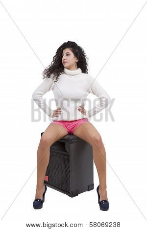 Young female fashion model sitting on a speaker