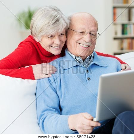 Amused Senior Couple Using A Laptop Computer