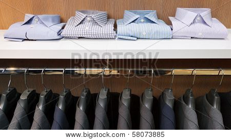 Row Of Men Suit Jackets On Hangers And Shelf With Shirt
