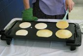 picture of pancake flip  - A woman with a spatula prepares to flip the pancakes cooking on a griddle - JPG