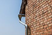pic of gutter  - Corner of an old brick house with gutters on a background of blue sky - JPG