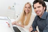 foto of turn-up  - Young couple or business partners working together at a laptop in an office turning to give the camera warm friendly smiles - JPG