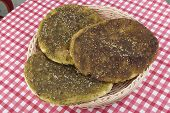 stock photo of pita  - Pita bread with zaatar green middle eastern herb on red table - JPG
